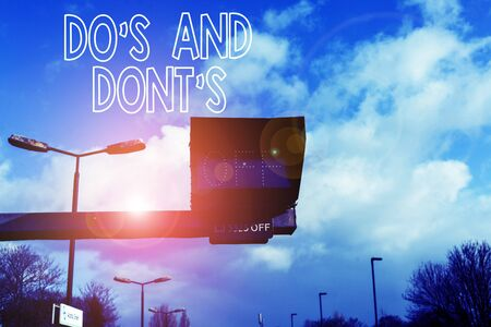 Conceptual hand writing showing Do S Is And Dont S Is. Concept meaning advising Rules or customs concerning some activity Front view lamp post with two lamps sunny day sky background