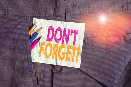 Text sign showing Don T Forget. Business photo showcasing used to remind someone about important fact or detail Writing equipment and white note paper inside pocket of man work trousers Foto de archivo
