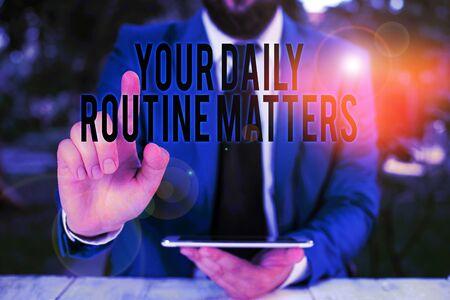 Wort schreiben Text Ihre tägliche Routine ist wichtig. Geschäftsfoto, das die Praxis zeigt, regelmäßig Dinge in fester Reihenfolge zu tun Geschäftsmann mit Zeigefinger vor ihm Standard-Bild