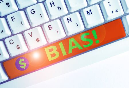 Conceptual hand writing showing Bias. Concept meaning inclination or prejudice for or against one demonstrating group White pc keyboard with note paper above the white background 版權商用圖片