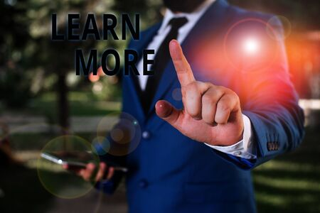 Word writing text Learn More. Business photo showcasing knowledge or skill acquired by instruction Considerable learning Businessman with pointing finger in front of him Stok Fotoğraf