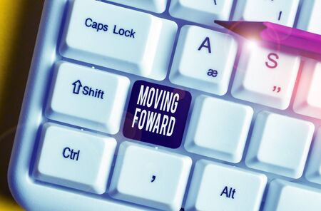 Handwriting text writing Moving Foward. Conceptual photo Towards a Point Move on Going Ahead Further Advance Progress White pc keyboard with empty note paper above white background key copy space