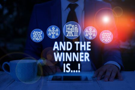 Text sign showing And The Winner Is. Business photo text announcing who got first place at competition or exam Male human wear formal work suit presenting presentation using smart device