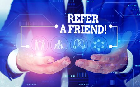 Conceptual hand writing showing Refer A Friend. Concept meaning direct someone to another or send him something like gift Male wear formal suit presenting presentation smart device Foto de archivo