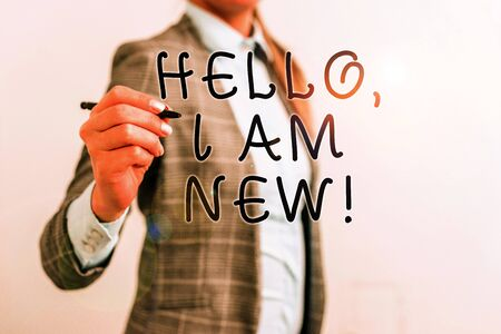 Writing note showing Hello I Am New. Business concept for introducing oneself in a group as fresh worker or student Business woman pointing in empty space with pen 版權商用圖片