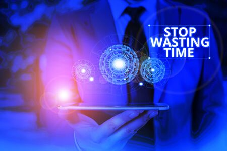 Conceptual hand writing showing Stop Wasting Time. Concept meaning advising demonstrating or group start planning and use it wisely Male wear formal suit presenting presentation smart device