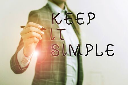 Writing note showing Keep It Simple. Business concept for to make something easy to understand and not in fancy way Business woman pointing in empty space with pen