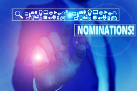 Text sign showing Nominations. Business photo showcasing action of nominating or state being nominated for prize Male human wear formal work suit presenting presentation using smart device 版權商用圖片 - 131568866