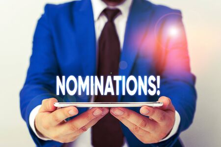 Handwriting text writing Nominations. Conceptual photo action of nominating or state being nominated for prize Businessman in blue suite with a tie holds lap top in hands 版權商用圖片 - 131569654