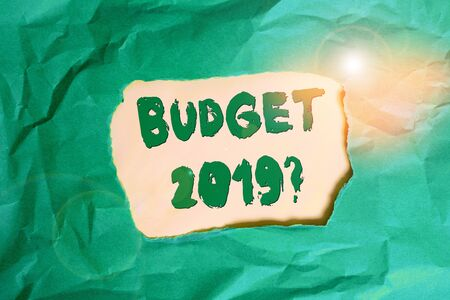 Writing note showing Budget 2019 Question. Business concept for estimate of income and expenditure for next year Green crumpled colored paper sheet torn colorful background