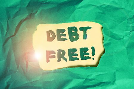 Writing note showing Debt Free. Business concept for does not owning any money to any individual or companies Green crumpled colored paper sheet torn colorful background Stok Fotoğraf