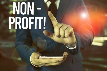 Text sign showing NonProfit. Business photo showcasing not making or conducted primarily to make profit organization Man with opened hands stands in suite. Concept with copy space and man