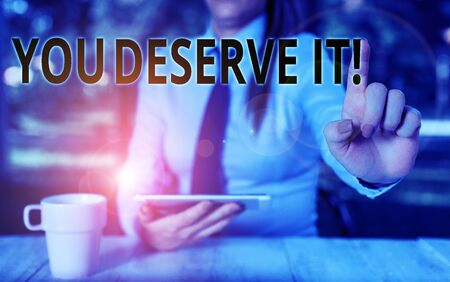Conceptual hand writing showing You Deserve It. Concept meaning should have it because of their qualities or actions Female business person sitting by table and holding mobile phone