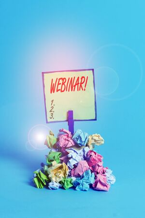 Conceptual hand writing showing Webinar. Concept meaning a seminar or other presentation that takes place on the Internet Reminder pile colored crumpled paper clothespin wooden space 版權商用圖片