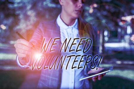 Text sign showing We Need Volunteers. Business photo text someone who does work without being paid for it Outdoor background with business woman holding lap top and pen