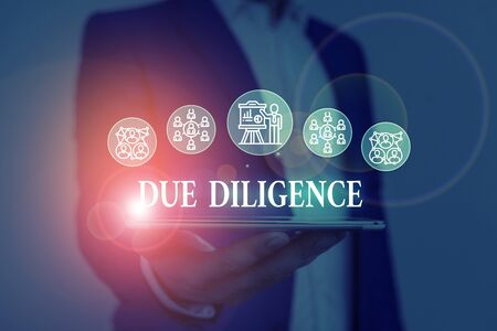 Text sign showing Due Diligence. Business photo showcasing Comprehensive Appraisal Voluntary Investigation Audit Male human wear formal work suit presenting presentation using smart device