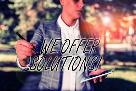 Text sign showing We Offer Solutions. Business photo text way to solve problem or deal with difficult situation Outdoor background with business woman holding lap top and pen Фото со стока