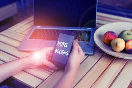 Conceptual hand writing showing Hotel Booking. Concept meaning Online Reservations Presidential Suite De Luxe Hospitality woman with laptop smartphone and office supplies technology