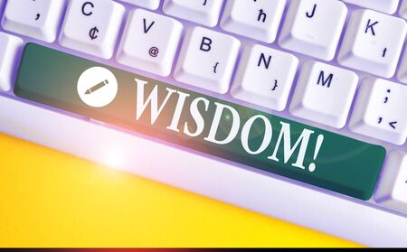 Writing note showing Wisdom. Business concept for quality having experience knowledge and good judgement something White pc keyboard with note paper above the white background
