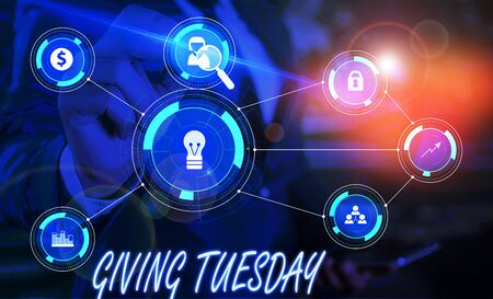 Writing note showing Giving Tuesday. Business concept for international day of charitable giving Hashtag activism Male wear formal suit presenting presentation smart device