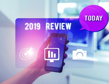 Text sign showing 2019 Review. Business photo text New trends and prospects in tourism or services for 2019 woman icons smartphone speech bubble office supplies technological device Stock Photo