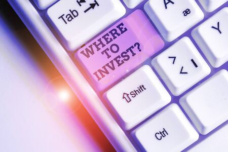 Word writing text Where To Invest question. Business photo showcasing asking about actions or process of making more money White pc keyboard with empty note paper above white background key copy space Stok Fotoğraf