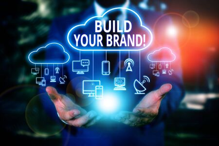 Writing note showing Build Your Brand. Business concept for creates or improves customers knowledge and opinions of product Male wear formal work suit presenting presentation smart device