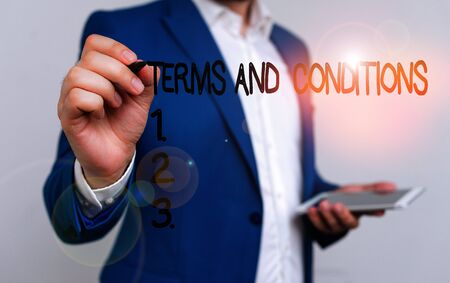 Conceptual hand writing showing Terms And Conditions. Concept meaning rules that apply to fulfilling a particular contract Businessman blue suite and white shirt pointing with finger