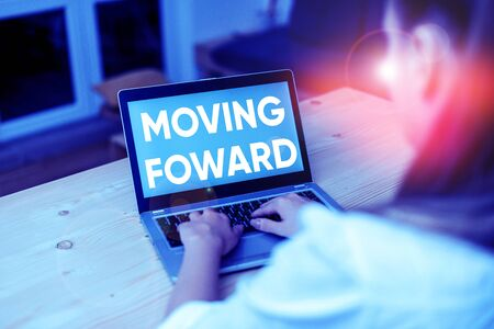 Conceptual hand writing showing Moving Foward. Concept meaning Towards a Point Move on Going Ahead Further Advance Progress woman with laptop smartphone and office supplies technology Stock fotó