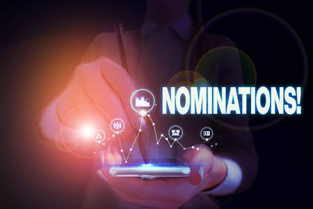 Writing note showing Nominations. Business concept for action of nominating or state being nominated for prize Woman wear formal work suit presenting presentation using smart device Фото со стока