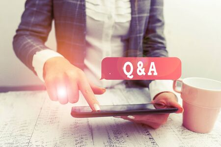 Handwriting text writing Q And A. Conceptual photo defined as questions being asked and answers Business concept with mobile phone in the hand Imagens