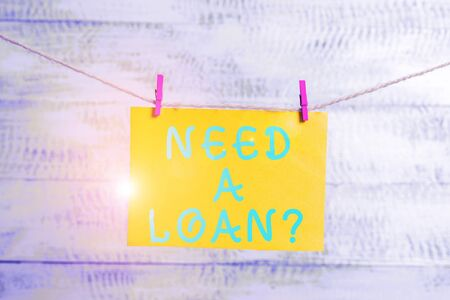 Conceptual hand writing showing Need A Loan question. Concept meaning amount of money that is borrowed often from bank Clothespin rectangle shaped paper reminder white wood desk