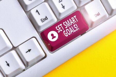 Writing note showing Set Smart Goals. Business concept for list to clarify your ideas focus efforts use time wisely White pc keyboard with note paper above the white background