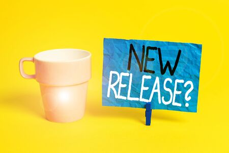 Handwriting text New Release Question. Conceptual photo asking about recent product or service newly unleashed Cup empty paper blue clothespin rectangle shaped reminder yellow office