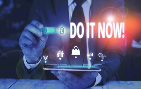 Writing note showing Do It Now. Business concept for not hesitate and start working or doing stuff right away Male wear formal suit presenting presentation smart device