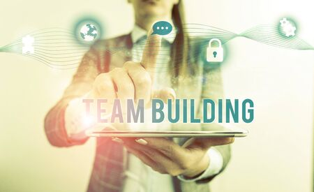 Conceptual hand writing showing Team Building. Concept meaning various types of activities used to enhance social relations Female human wear formal work suit presenting smart device Stock Photo