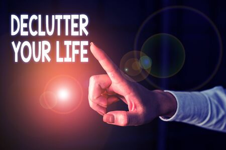 Writing note showing Declutter Your Life. Business concept for To eliminate extraneous things or information in life Finger pointing in the Dark with hand pointing in the copy space Stok Fotoğraf