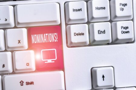 Conceptual hand writing showing Nominations. Concept meaning action of nominating or state being nominated for prize White pc keyboard with note paper above the white background