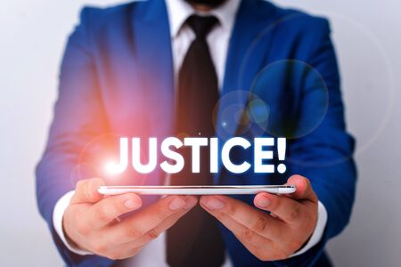 Handwriting text writing Justice. Conceptual photo impartial adjustment of conflicting claims or assignments Businessman in blue suite with a tie holds lap top in hands