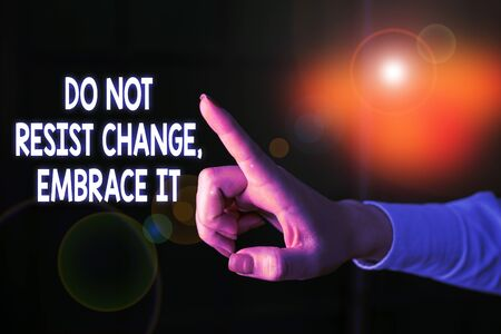 Writing note showing Do Not Resist Change Embrace It. Business concept for Be open to changes try new things Positive Finger pointing in the Dark with hand pointing in the copy space Imagens