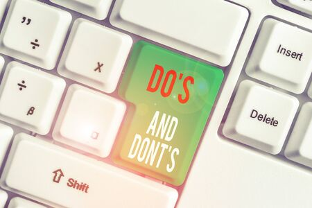 Text sign showing Do S Is And Dont S Is. Business photo showcasing advising Rules or customs concerning some activity White pc keyboard with empty note paper above white background key copy space 스톡 콘텐츠