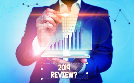 Writing note showing 2019 Review Question. Business concept for remembering past year events main actions or good shows bar char improvement line smartphone computer office technology device