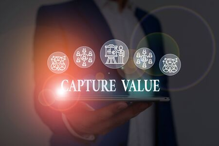 Text sign showing Capture Value. Business photo showcasing Customer Relationship Satisfy Needs Brand Strength Retention Male human wear formal work suit presenting presentation using smart device Stock Photo