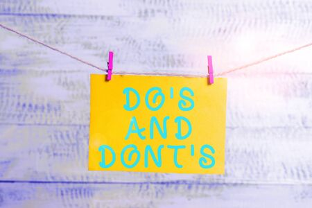 Conceptual hand writing showing Do S Is And Dont S Is. Concept meaning advising Rules or customs concerning some activity Clothespin rectangle shaped paper reminder white wood desk 스톡 콘텐츠