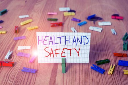 Text sign showing Health And Safety question. Business photo text regulations and procedures intended to prevent accident Colored clothespin papers empty reminder wooden floor background office Banque d'images - 131758711