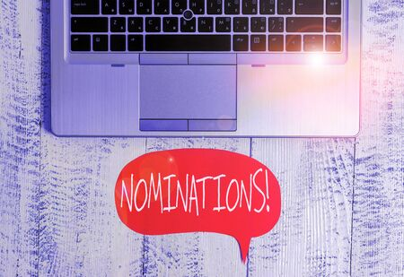 Writing note showing Nominations. Business concept for action of nominating or state being nominated for prize Close view open laptop speech bubble downwards lying vintage table