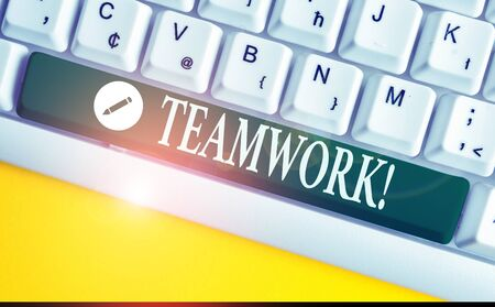 Writing note showing Teamwork. Business concept for combined action of group especially when effective and efficient White pc keyboard with note paper above the white background 版權商用圖片
