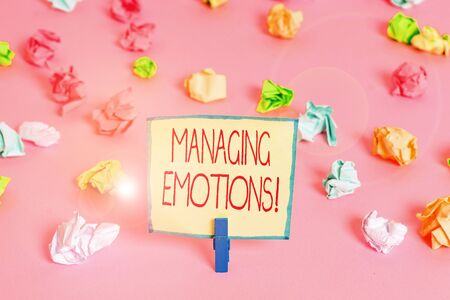 Text sign showing Managing Emotions. Business photo text ability be open to feelings and modulate them in oneself Colored crumpled papers empty reminder pink floor background clothespin Stock fotó