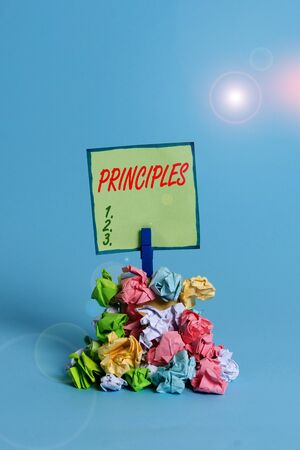 Conceptual hand writing showing Principles. Concept meaning fundamental truth that serves as the base for a system of belief Reminder pile colored crumpled paper clothespin wooden space