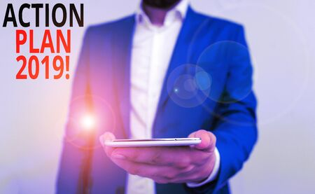 Word writing text Action Plan 2019. Business photo showcasing proposed strategy or course of actions for current year Business concept with man holding mobile phone with touch screen
